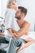 giovani coppie appassionate con preservativo che si siede sul letto