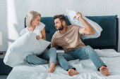 cheerful boyfriend and girlfriend fighting with pillows on bed in bedroom
