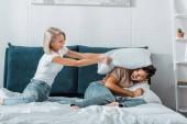 radost přítelkyni výprask přítel s polštářem na lůžku v ložnici