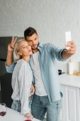young couple grimacing and taking selfie with smartphone in kitchen