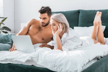 Beautiful young couple using laptop together in bedroom stock vector