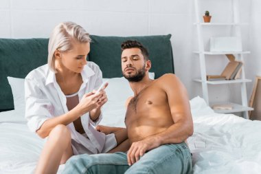 jealousy young woman using smartphone of her confused boyfriend in bedroom