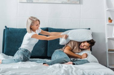 happy girlfriend beating boyfriend with pillow on bed in bedroom