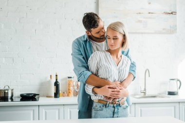 sensual boyfriend hugging girlfriend from back in kitchen