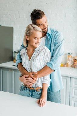 sensual smiling boyfriend hugging girlfriend from back in kitchen