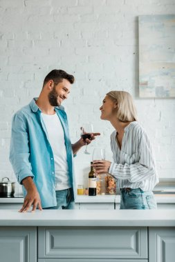 Smiling young couple talking, holding glasses of red wine and looking at each other in kitchen stock vector