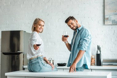Smiling young couple showing glasses of red wine and looking at camera in kitchen stock vector