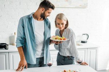 boyfriend showing salad on plate to attractive girlfriend in kitchen