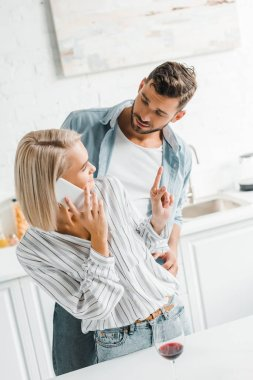 young girlfriend talking by smartphone and showing one finger up to boyfriend in kitchen