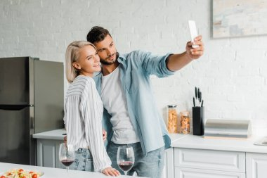 Cheerful young couple taking selfie with smartphone in kitchen stock vector