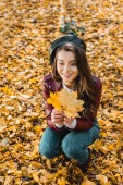 Fotografie beautiful female model in beret and leather jacket sitting with yellow in autumnal park