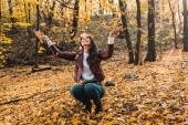 lächelnde attraktive Frau in stylischer Lederjacke, die Spaß mit gelben Blättern im herbstlichen Wald hat