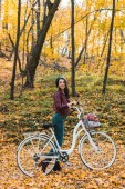 Photo happy fashionable woman in stylish leather jacket and beret carrying bicycle in forest