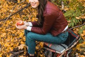 Fotografie partial view of stylish girl in leather jacket sitting on blanket and holding red apple in autumnal forest