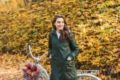 Happy krásná žena stojící poblíž kolo s košíkem plné jablek v podzimní les