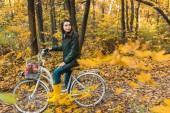 Veselá mladá žena sedí na kole s koš plný jablek v žluté podzimní les