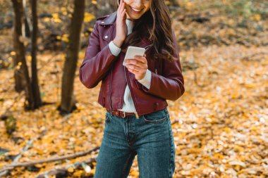 cropped image of smiling woman in stylish leather jacket using smartphone in autumnal forest