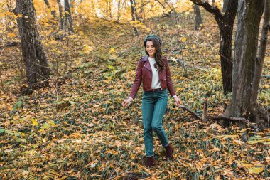 fashionable young woman in leather jacket and beret walking down in autumnal park