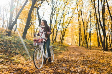 Selective focus of happy girl in leather jacket and beret riding on bicycle in yellow autumnal forest stock vector