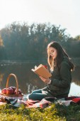 side view of attractive young woman with coffee cup reading book on blanket near pond in park