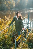 Photo side view of young woman in jacket and yellow rubber boots posing near pond in park