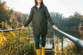 Photo partial view of young woman in jacket and yellow rubber boots posing near pond in park