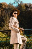 Selektiver Fokus einer jungen attraktiven Frau mit Hut und Sonnenbrille, die im Freien in die Kamera blickt