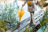 Photo cropped image of fashionable woman in trench coat standing with yellow umbrella near pond