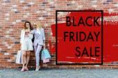 Fotografie schockiert junge Frauen mit Einkaufstaschen Selfie vor Ziegel Wand, schwarzen Freitag verkaufen Banner steht unter