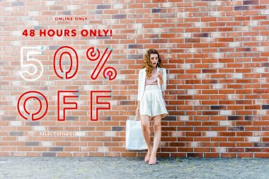 shocked young woman with shopping bags using smartphone in front of brick wall, sale banner