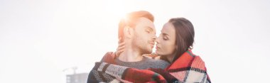 panoramic shot of beautiful young couple covering in plaid and kissing with sun shining behind