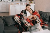 beautiful young couple with glasses of white wine relaxing on couch under plaid
