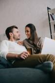 Fényképek boldog, fiatal pár, így e-vásárlás-laptop otthon a kanapén Alulnézet