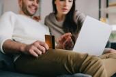Fényképek gyönyörű fiatal pár, így e-shopping-arany hitelkártya és laptop otthon a kanapén