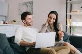 Fényképek boldog, fiatal pár, így e-vásárlás-laptop otthon a kanapén