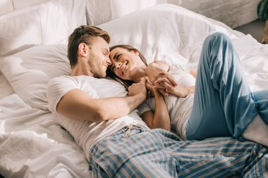 beautiful young couple in pajamas cuddling in bed in morning