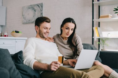 smiling young couple making e-shopping with laptop on couch at home