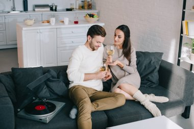 High angle view of happy young couple listening music with vinyl record player and drinking wine at home stock vector