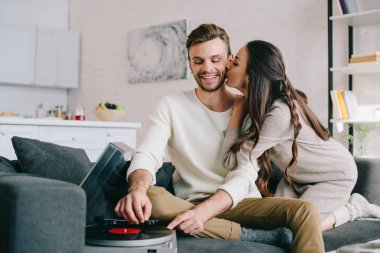 happy young couple listening music with vinyl record player and cuddling at home