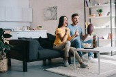Fotografie expressive young couple cheering for american football game at home