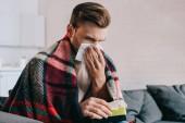 Fotografie Kranker junger Mann niest mit Papierservietten auf Couch