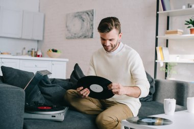 handsome young man holding disc for vinyl record player while sitting on couch