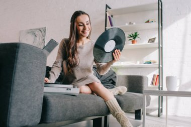 happy young woman listening music with vinyl record player on couch at home