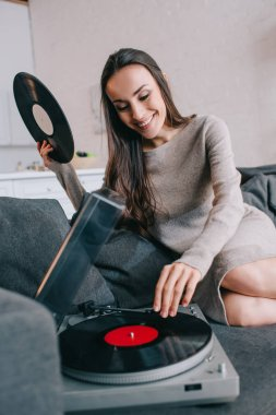 smiling young woman listening music with vinyl record player on couch at home