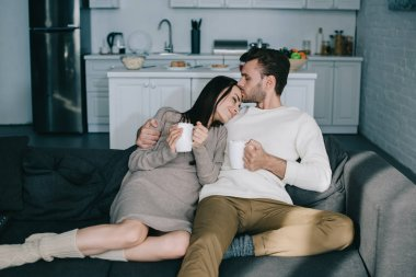 beautiful young couple with cups of cocoa with marshmallow cuddling on couch at home