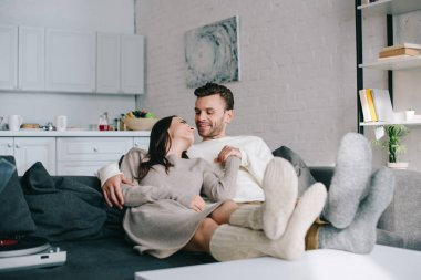 happy couple in woolen socks relaxing on couch at home