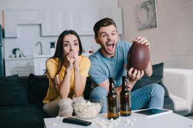 expressive young couple cheering for american football game at home