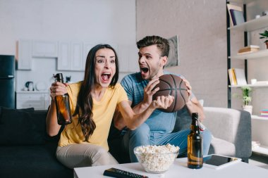 shouting young couple with beer cheering for basketball game at home