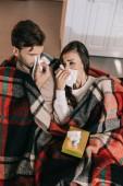 krank junges Paar mit Papierservietten Niesen auf Couch unter Plaid zu Hause
