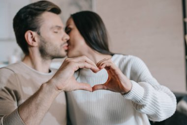 beautiful young couple kissing and making heart symbol with hands